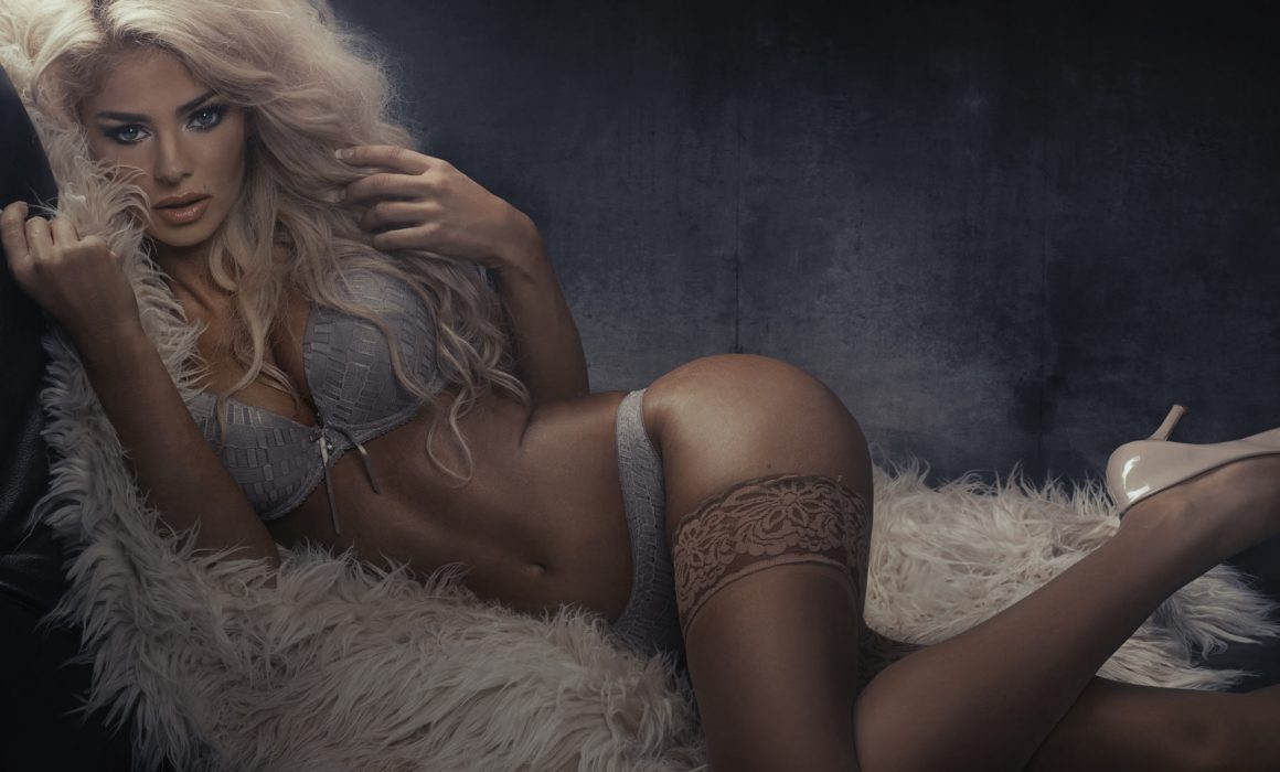 Sexy blonde with stocking and panties lays on woolen rug