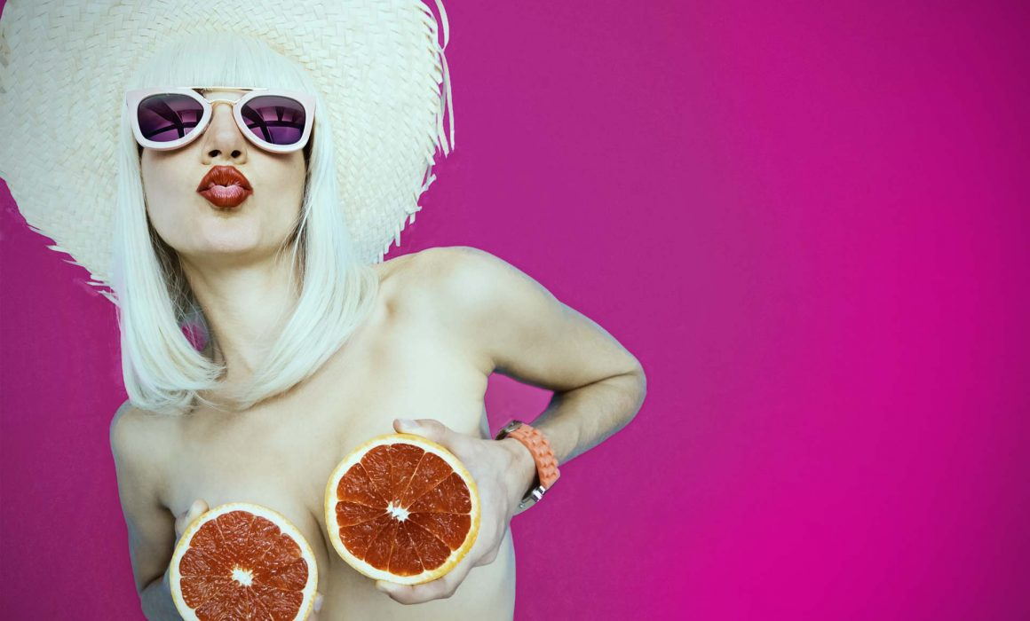 Sexy woman covers breasts with grapefruit
